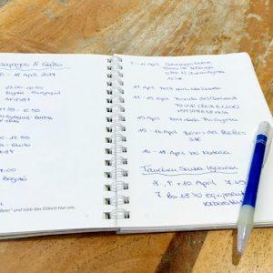 Reisetagebuch offen mit Stift auf Tisch