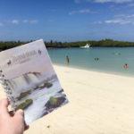 JourneyBook Reisetagebuch in der Hand gehalten mit Blick auf Meer