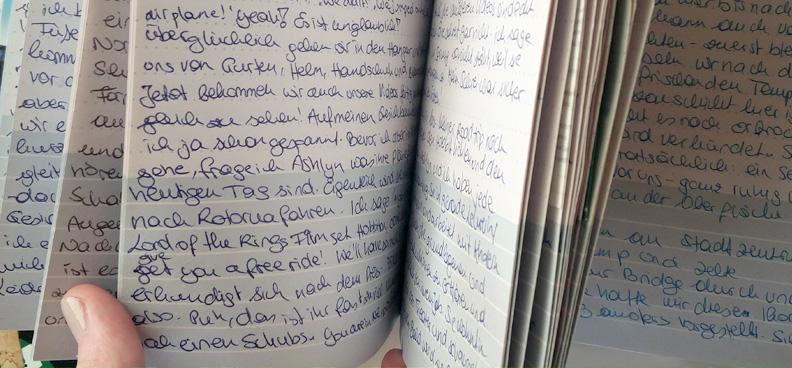 Hand blättert in handgeschriebenem Reisetagebuch